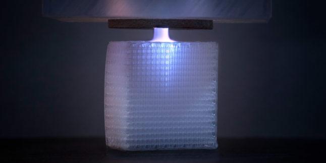 Auf dem Foto ist ein Plasmajet zu sehen, der auf ein würfelartiges Kunststoffgerüst trifft
