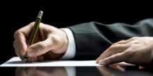 Hände im Anzug schreiben auf ein Blatt Papier