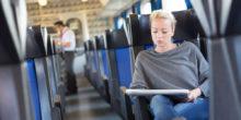 junge Frau sitzt in Zug, im Hintergrund sieht man einen Kontrolleur