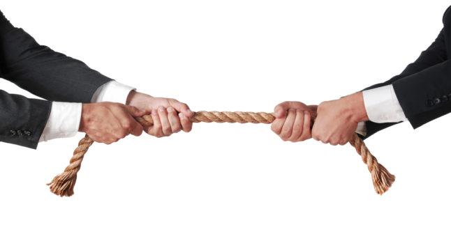 Zwei Arme im Anzug halten ein Seil fest - bereit zum Tauziehen