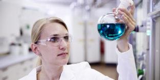 Eine Wissenschaftlerin hält einen Erlenmeyerkolben mit einer blau-durchsichtigen Flüssigkeit hoch