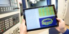 Zwei Hände halten ein Tablet, auf dem ein CAD-Programm zu sehen ist.