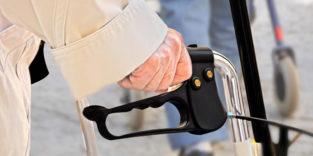 Die Hand eines Senioren umgreift den Griff eines Rollators.