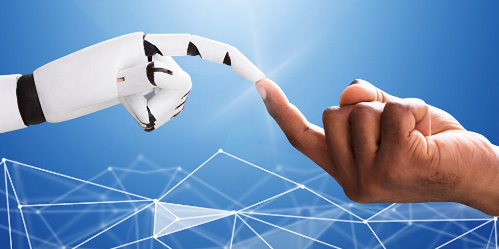 Man sieht eine Computerhand und eine Menschenhand, die sich berühren.