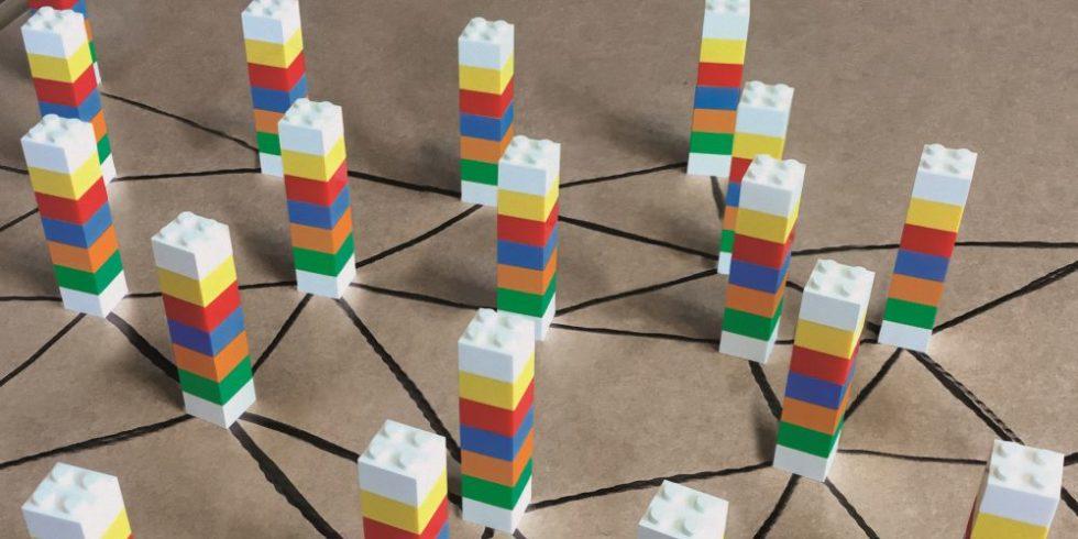 Bunte Legotürmchen sind durch Striche auf dem Boden verbunden und bilden so ein Netz