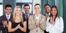 Ein Team aus sechs Personen in Businesskleidung applaudiert