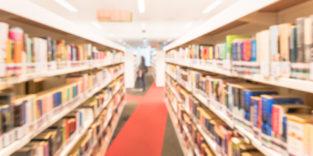 Blick in eine Bibliothek mit weißen Regalen rechts und links des Ganges
