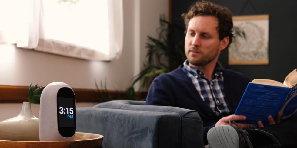 Der digitale Sprachassistent Mycroft Mark II steht auf einem Tisch, daneben ein Mann auf der Couch, der ihn ansieht