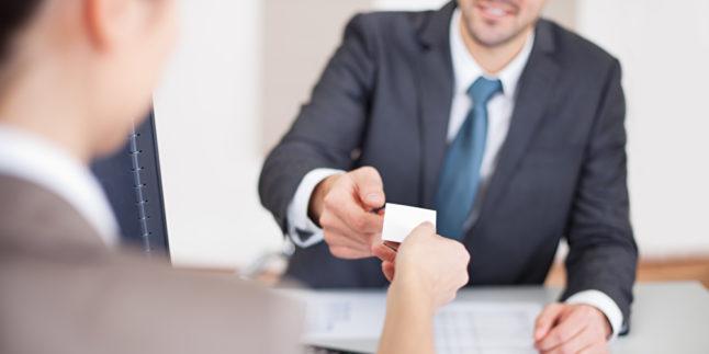 Frau reicht einem Mann eine Visitenkarte über den Tisch