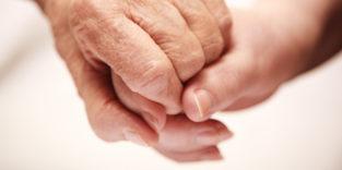 Symbolbild zum Thema Pflege von Angehörigen. Zwei Hände, eine junge und eine alte greifen ineinander