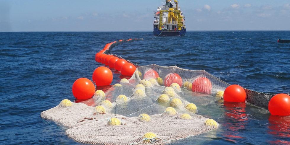 Man sieht ein Netz, das mit Ölbindern gefüllt im Wasser liegt.