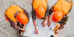 Drei Menschen mit Warnwesten und Bauhelmen beugen sich über einen Bauplan