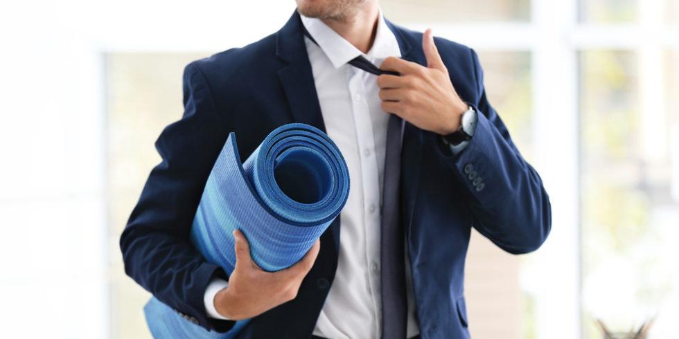 Mann im Anzug mit einer Yogamatte unter dem Arm steht symbolisch für betriebliches Gesundheitsmanagement