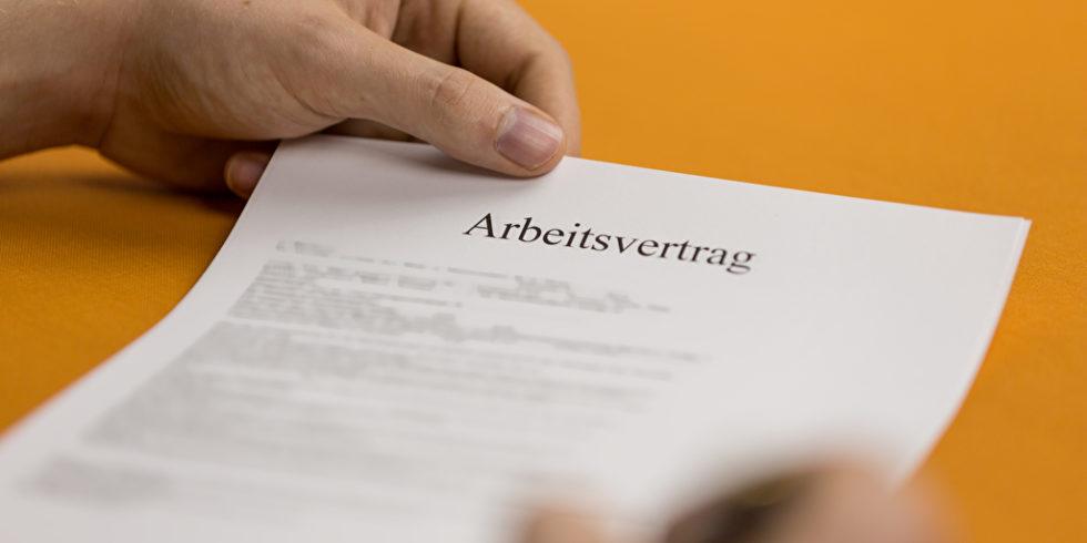 Ein Arbeitsvertrag liegt auf einem orangenen Tisch