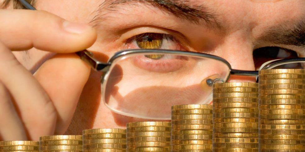 Mann mit Brille schaut auf gestapelte Münzen
