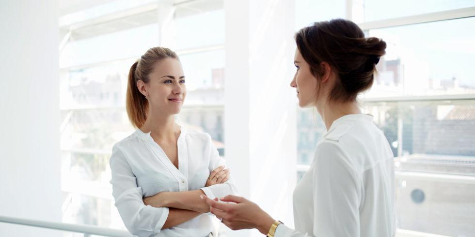 Jobsharing-Symbolbild. Zwei Geschäftsfrauen unterhalten sich vor Glasfassade