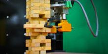 Industrieroboter greift Holzklötzchen beim Jenga-Spiel