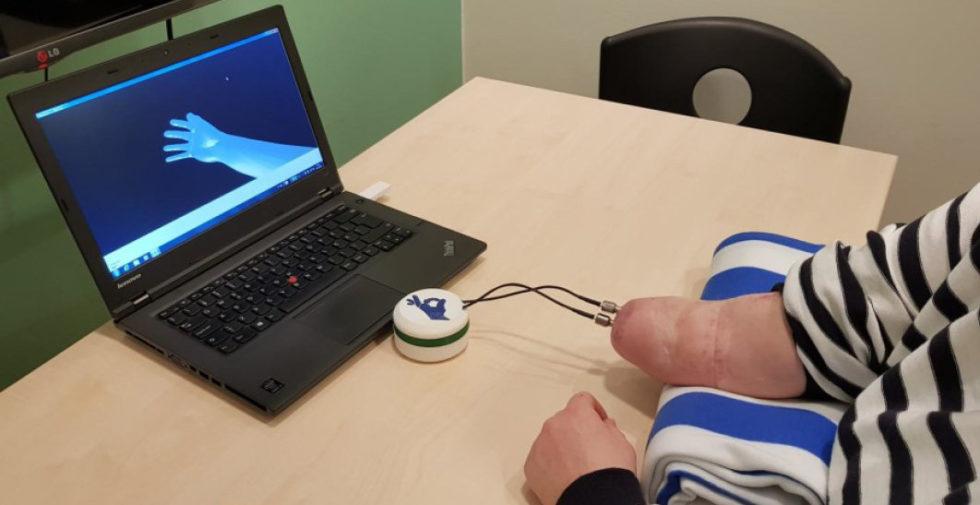 Patientin vorm Computer, die eine virtuelle Hand steuert