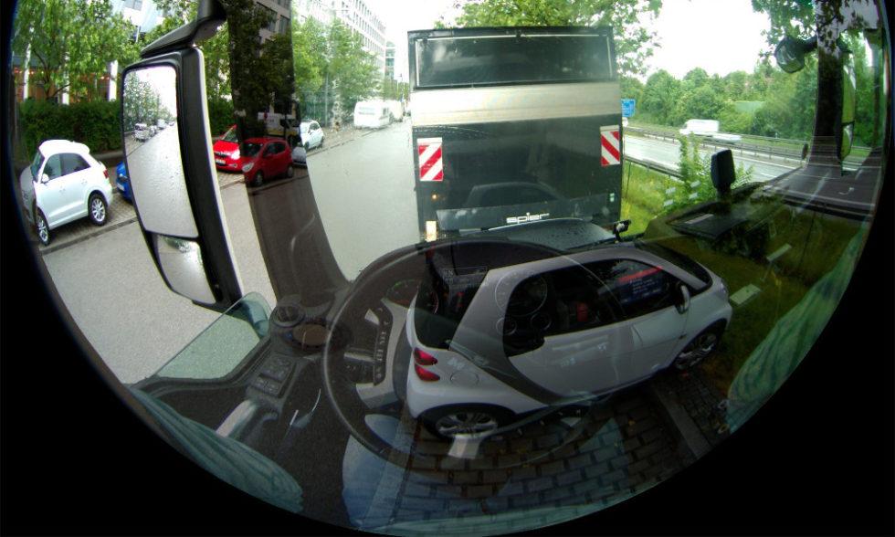 Simulierter Blick aus dem Fahrerhaus eines Lkw. Die Kameraaufnahme überlagert sich mit der Fahrerperspektive. Vorm Fahrzeug ist ein Pkw erkennbar, als wäre der Lkw transparent. Foto: Fraunhofer IOSB
