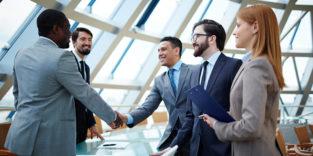 Verhandlung erfolgreich. Fünf Menschen stehen sich an einem Tisch gegenüber, zwei reichen sich die Hand