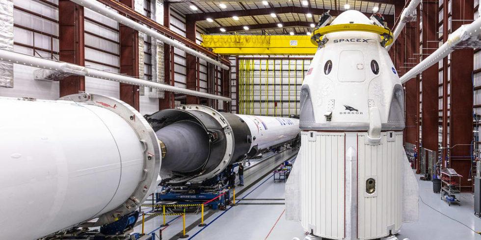 SpaceX-Raumkapsel Crew Dragon und die Falcon 9 Rakete stehen nebeneinander im Hangar
