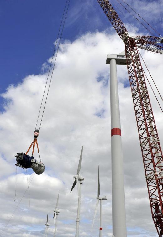Der Generator wird mithilfe eines Krans in die Anlagengondel eingebaut.
