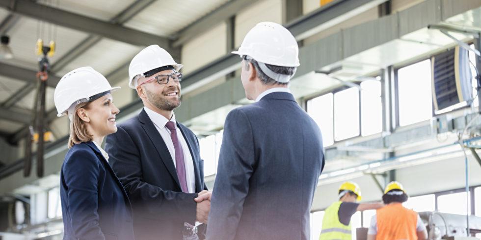 Geschäftspartner schütteln sich die Hände beim Abschluss eines Werkvertrags