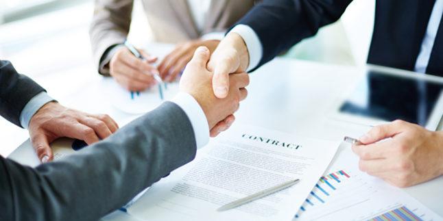 Menschen im Anzug schütteln sich die Hände über einem Arbeitsvertrag