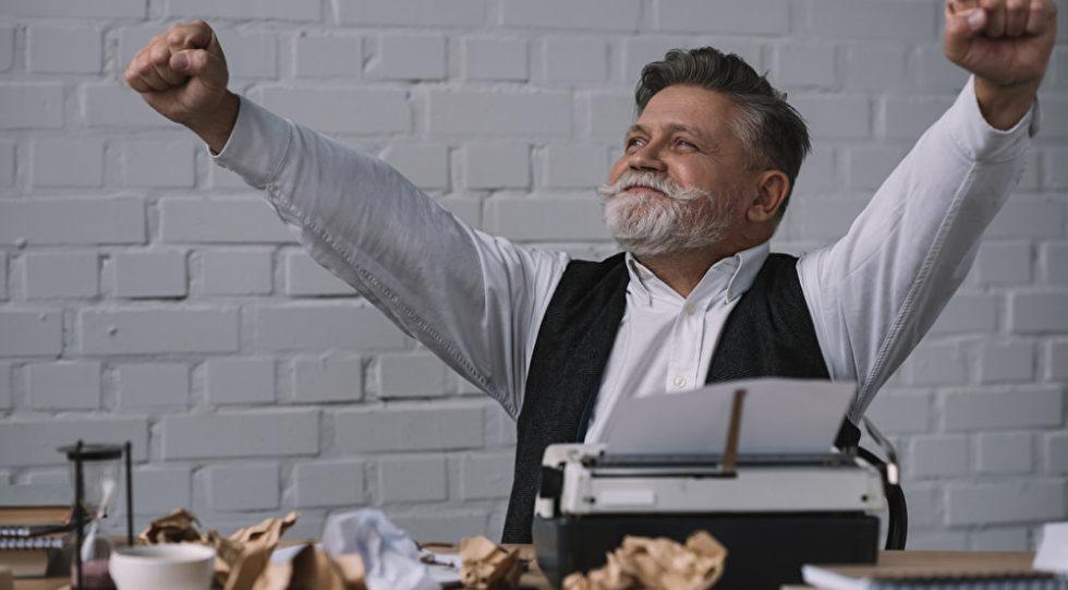 Ein Autor: Mann mit Schreibmaschine und zerknülltem Papier