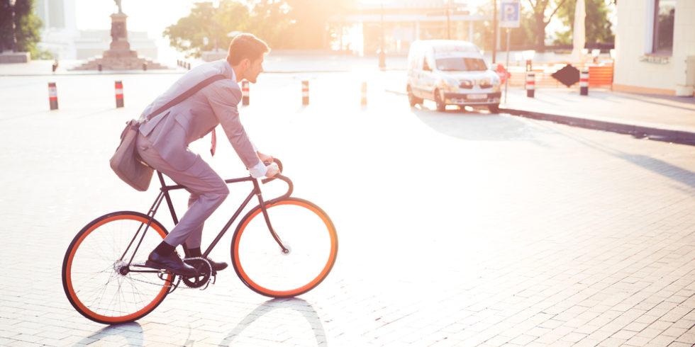 Mann im Anzug auf einem Dienstrad oder Jobrad bei Sonnenschein