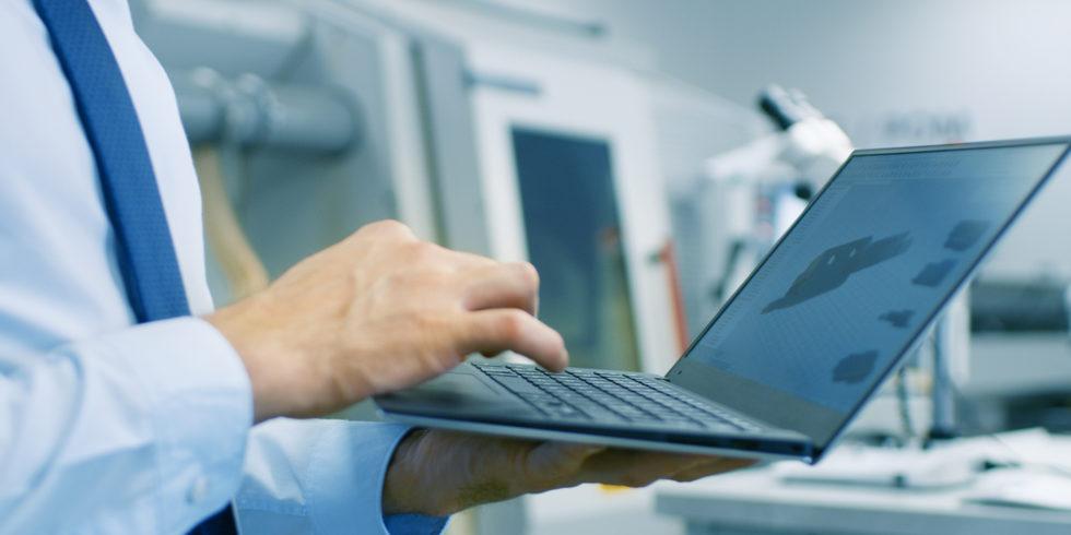 Digitales Arbeiten. Ein Mann steht mit Laptop in der Hand im Raum, dahinter eine industrieroboter