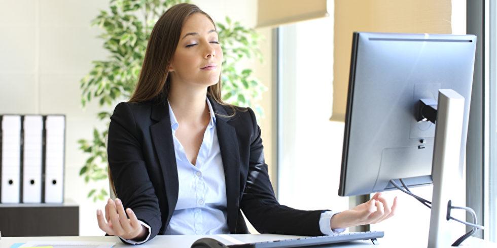 Frau sitzt vor Computer und meditiert