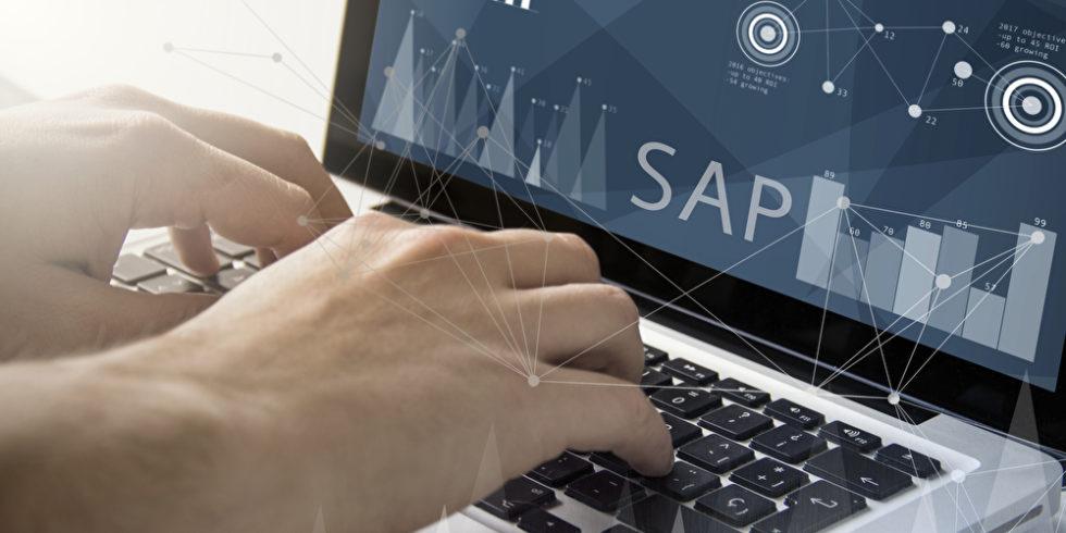 SAP steht auf einem Laptop, an dem Männerhände tippen