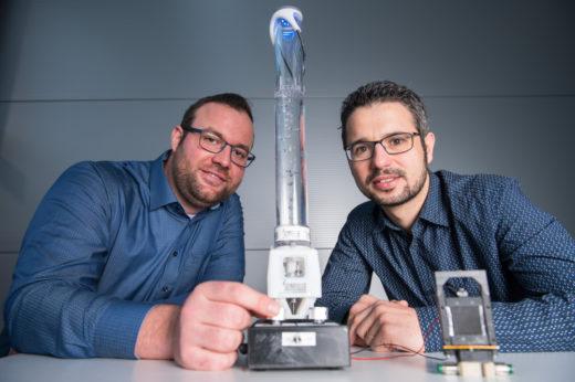 Zwei Forscher mit Prototypen einer motorlosen Pumpe und eines smarten Ventils aus Folie.