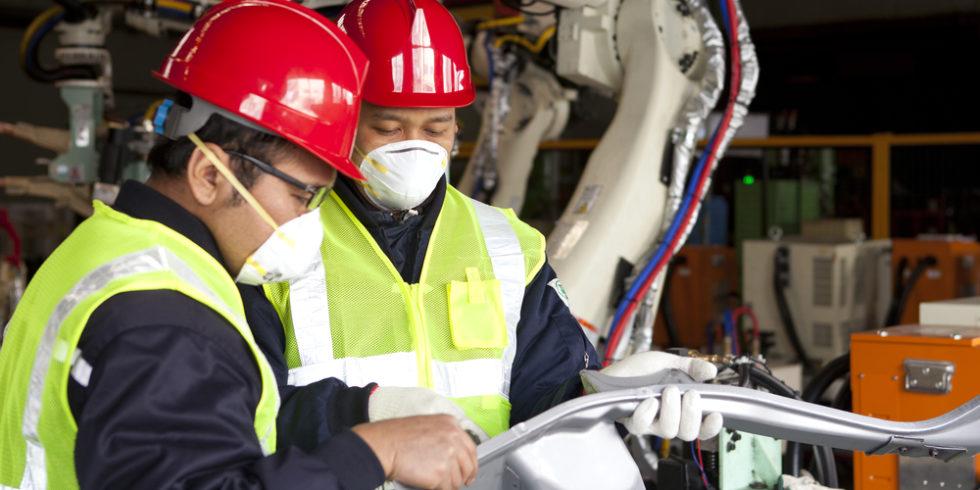 zwei Männer mit Warnwesten, Helmen und Mundschutz in der Fabrik. Im Hintergrund eine Maschine