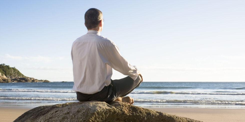 Meditierender Mann auf Felsen am Strand