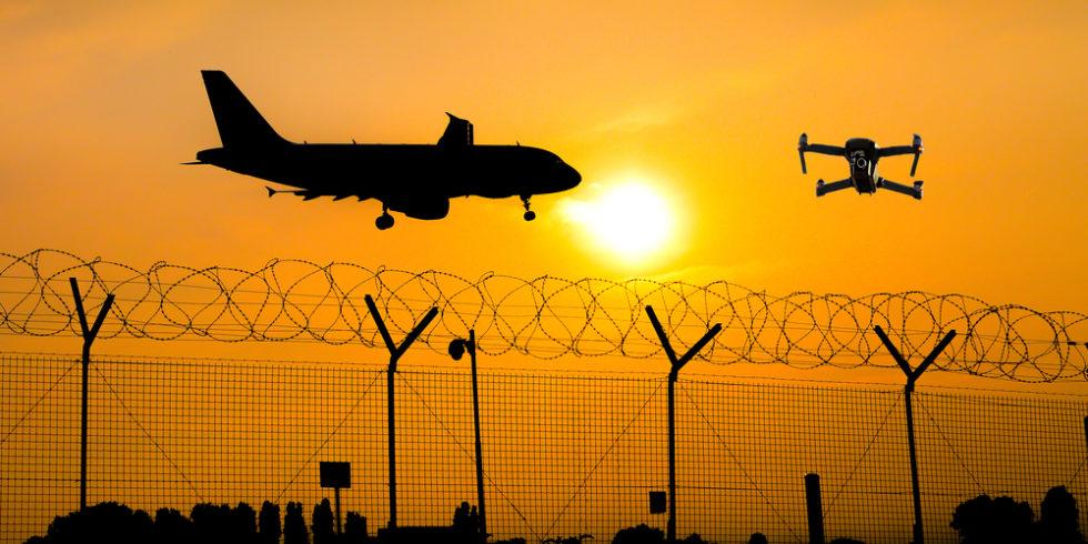 Flugzeug landet vor Abendsonne - mit im Bild ist eine Drohne