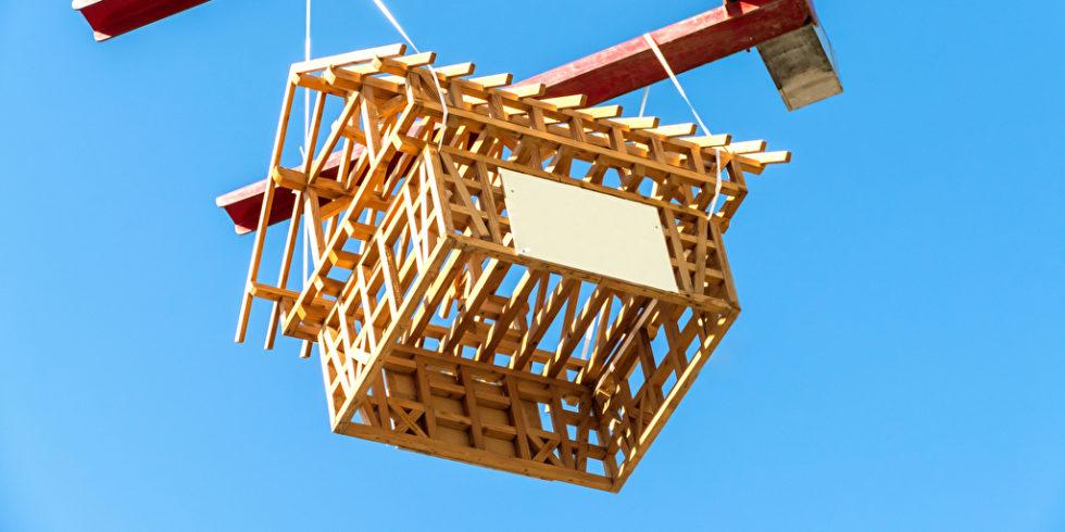 Holzhaus Grundstruktur hängt an einem Kran vor blauem Himmel