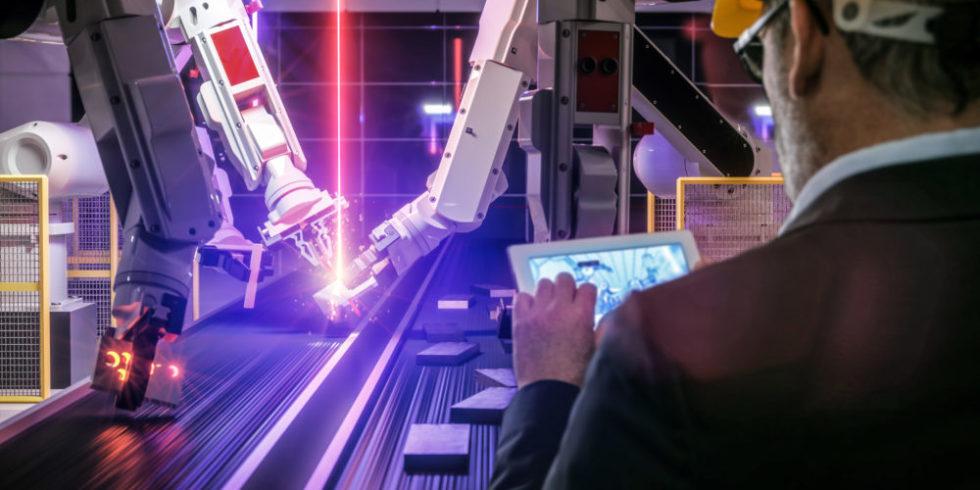 IoT-Ingenieur: Mann mit Tablet steht in der Produktion vor Robotern