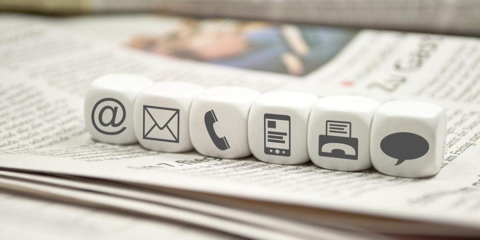 Schriftform, dargestellt durch Würfel mit @-, Brief-, Telefon- und Sprechblasen-Zeichen