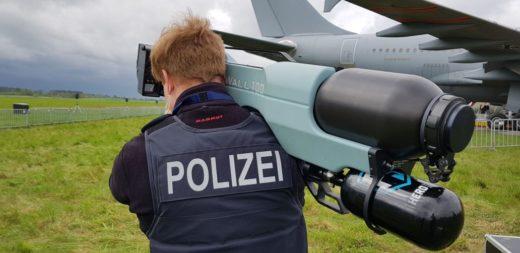 Mit einem Netzwerfer gegen Drohnen - Polizist schultert Netzwerfer-Kanone