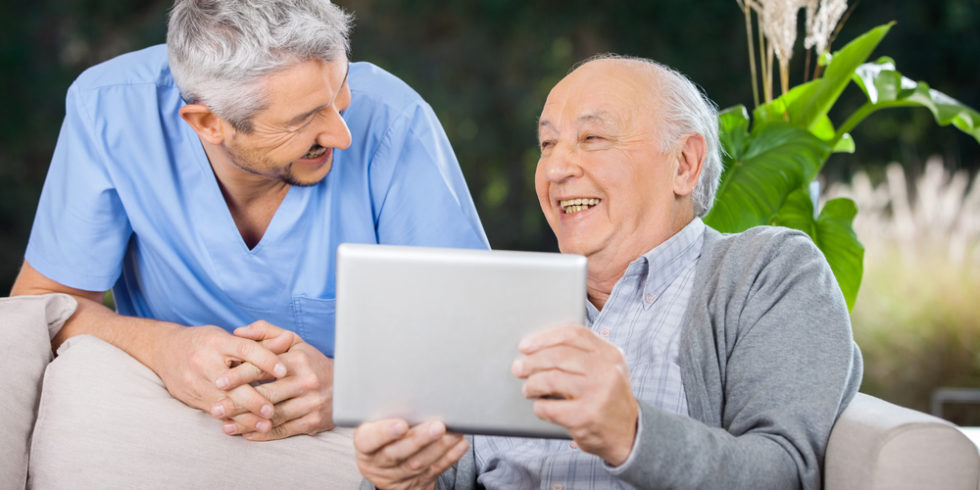 Zwei Männer schauen sich an, der ältere hält ein Tablet