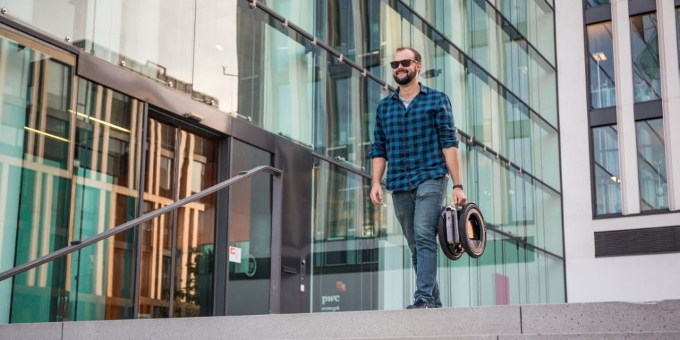 Mann trägt zusammengefaltetes Hoverboard wie eine Laptoptasche