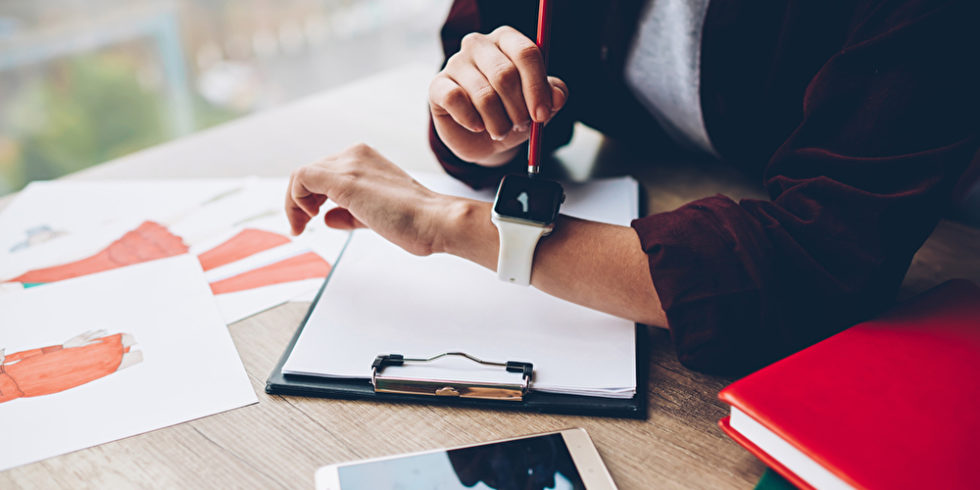 Zeiterfassung: Blick auf Frauenhände mit Smartwatch, daneben liegen auf dem Tisch Tablet und Notizpapier