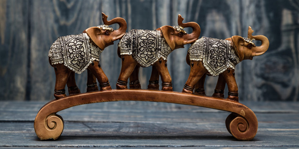 Drei Holzelefanten auf einer Holzbrücke