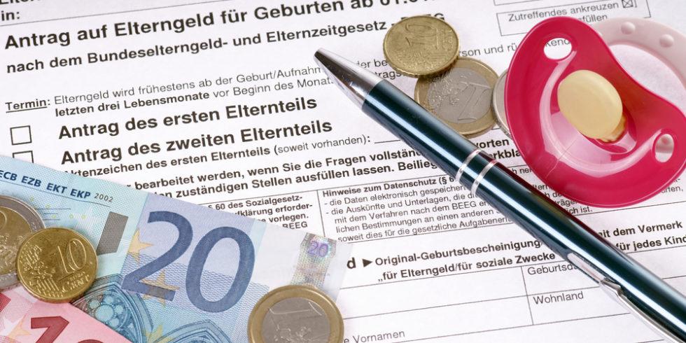Euroscheine und -münzen und Kuli und Schnuller liegen auf Antrag für Elterngeld