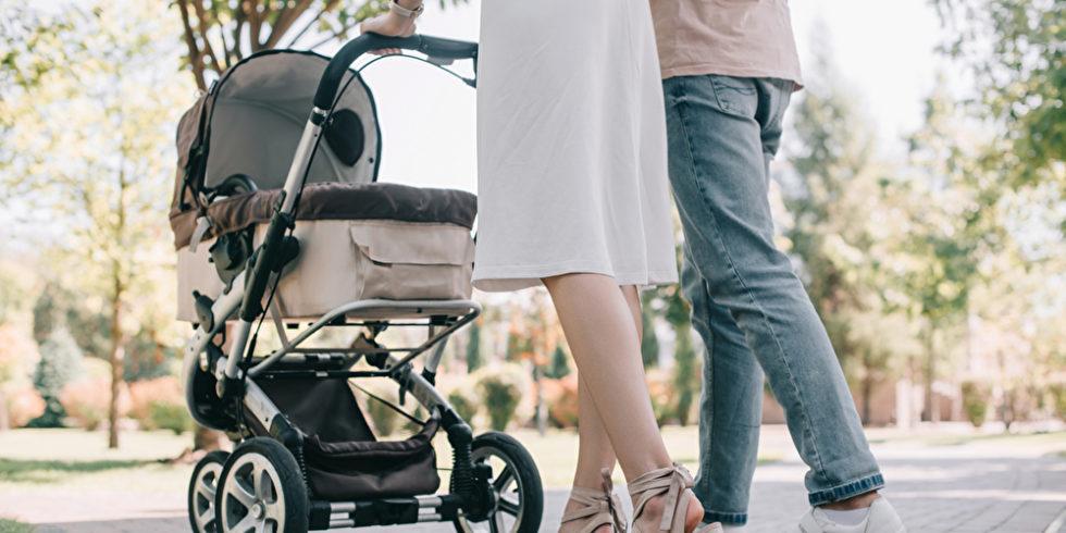 Frauen- und Männerbeine vor einem Kinderwagen