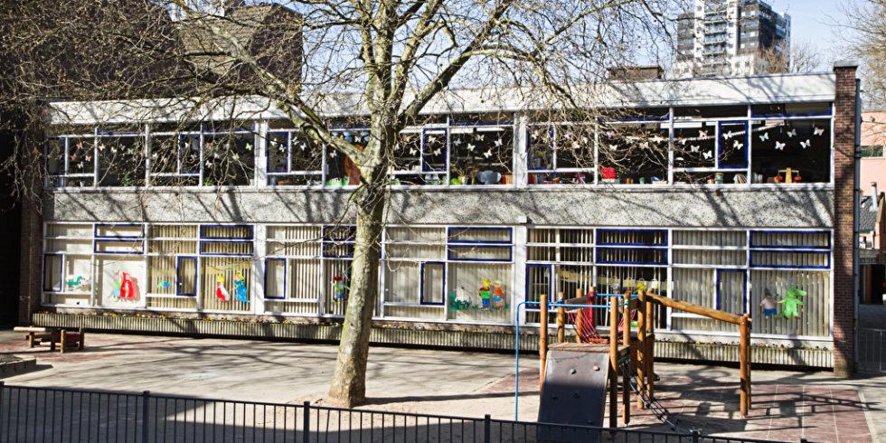 Gebäude mit vielen Bastelarbeiten in den Fenstern und Hof davor, vermutlich ein Kindergarten