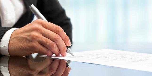 Frauenhand unterzeichnet ein Blatt Papier