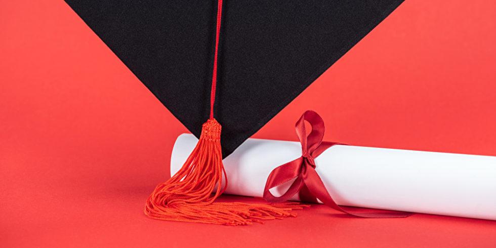 Diplomabschluss vor rotem Hintergrund
